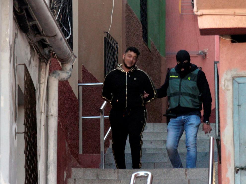 Un miembro de la Guardia Civil con uno de los detenidos durante la operación contra el tráfico de drogas y de inmigrantes que se ha iniciado en Ceuta y que se extiende a otras localidades, como Algeciras y Málaga.