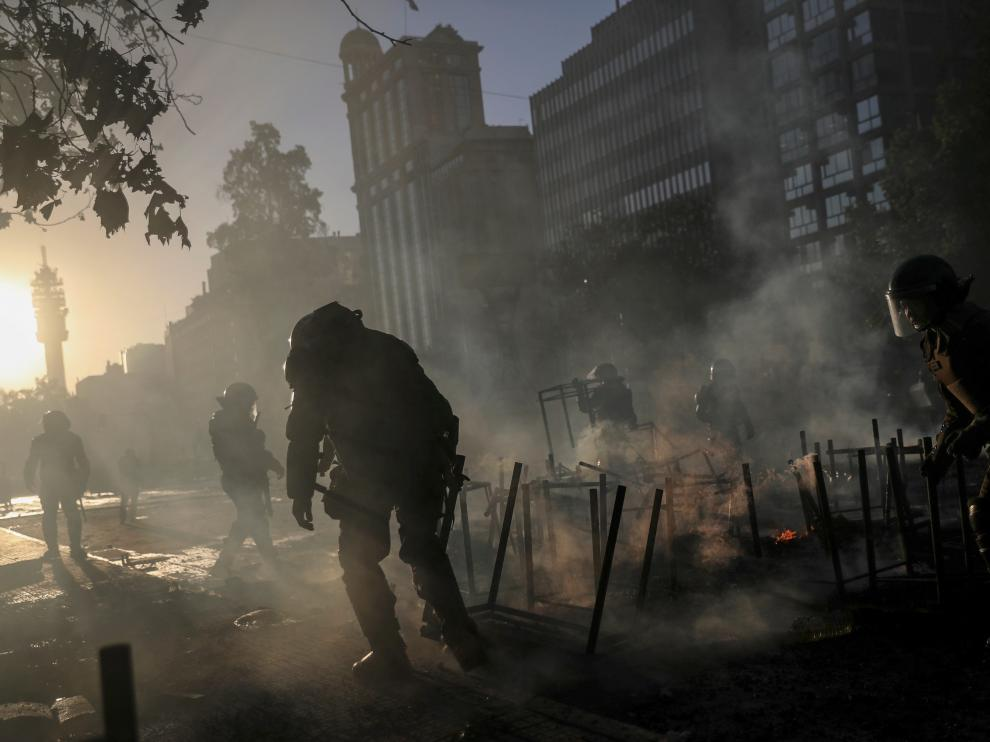 A demonstrator takes cover against a police water cannon during an anti-government protest in Santiago, Chile October 28, 2019. REUTERS/Henry Romero TPX IMAGES OF THE DAY [[[REUTERS VOCENTO]]] CHILE-PROTESTS/