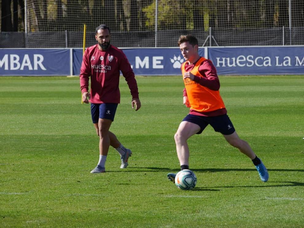 Sergio Gómez conduce el balón ante la mirada de Ivi, en el entrenamiento a puerta cerrada de este domingo.