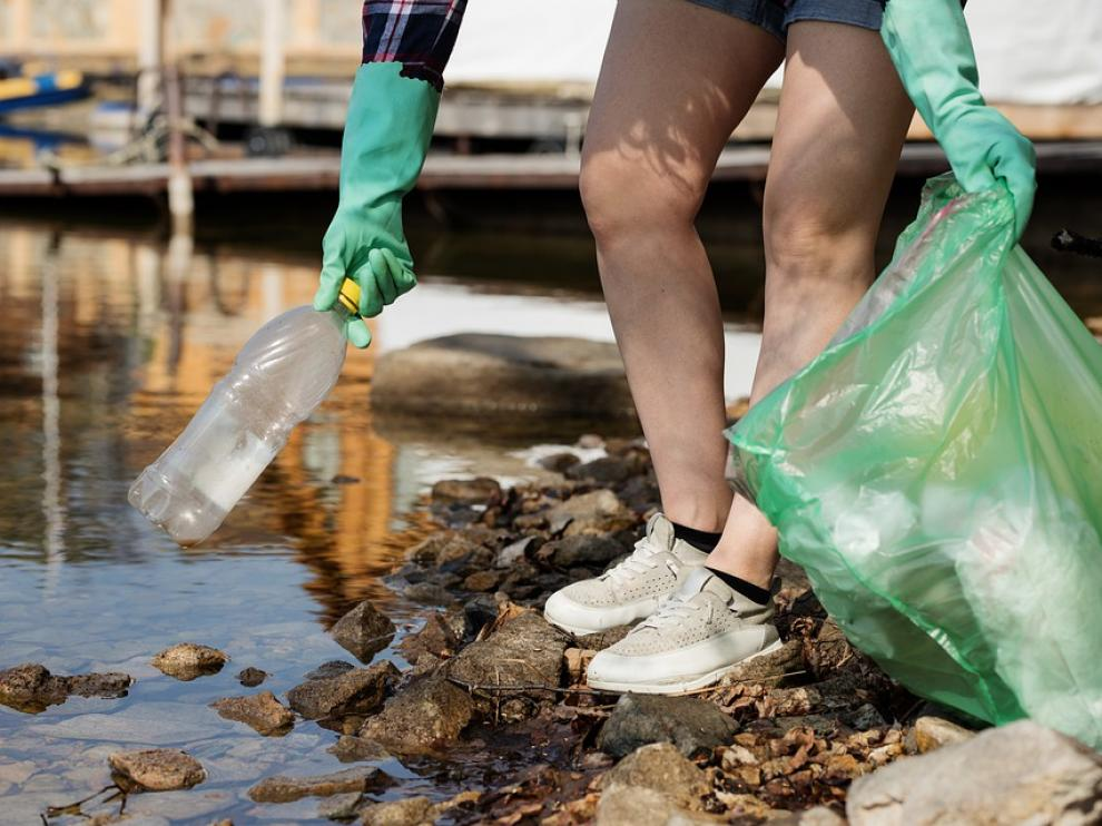 Una persona retira residuos de plástico.