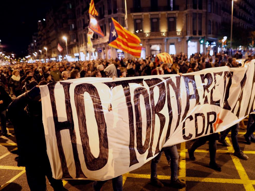 """Un grupo de CDR enmascarados tras la pancarta que reza """"lo volveremos a hacer""""."""