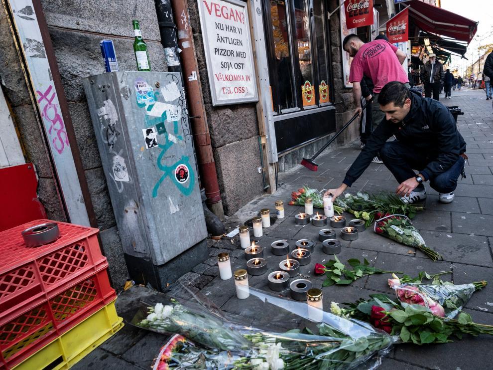 Un hombre coloca una vela en el lugar en el que el joven de 15 años fue asesinado en la ciudad sueca de Malmö.