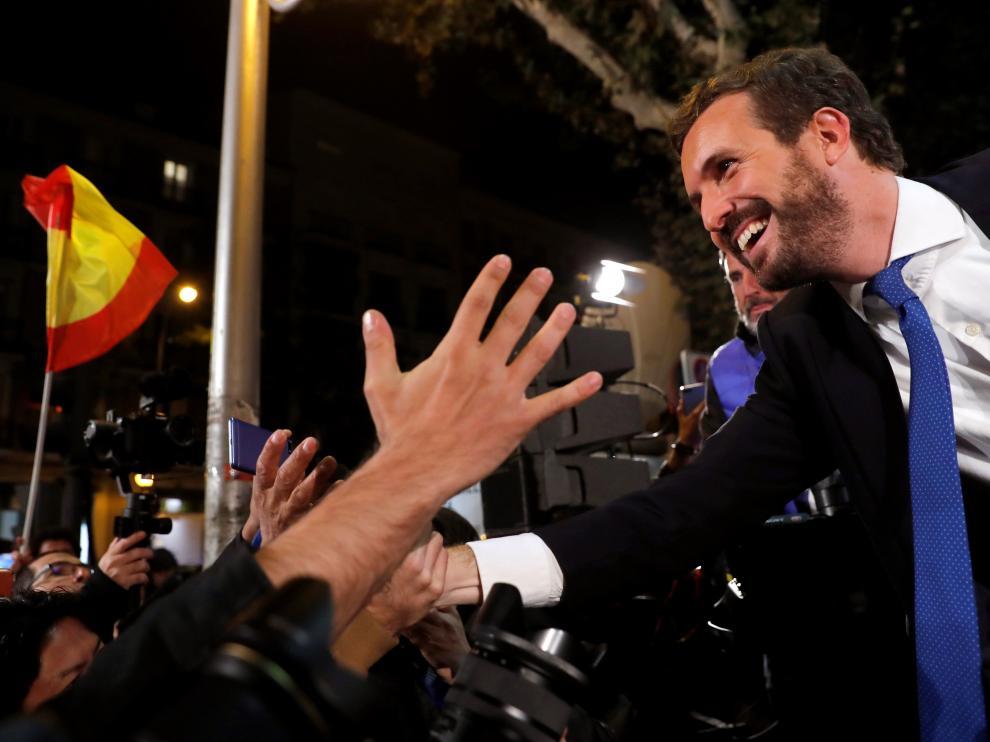 El líder del PP, Pablo Casado, saluda a sus simpatizantes en el exterior de la sede del partido en Madrid.