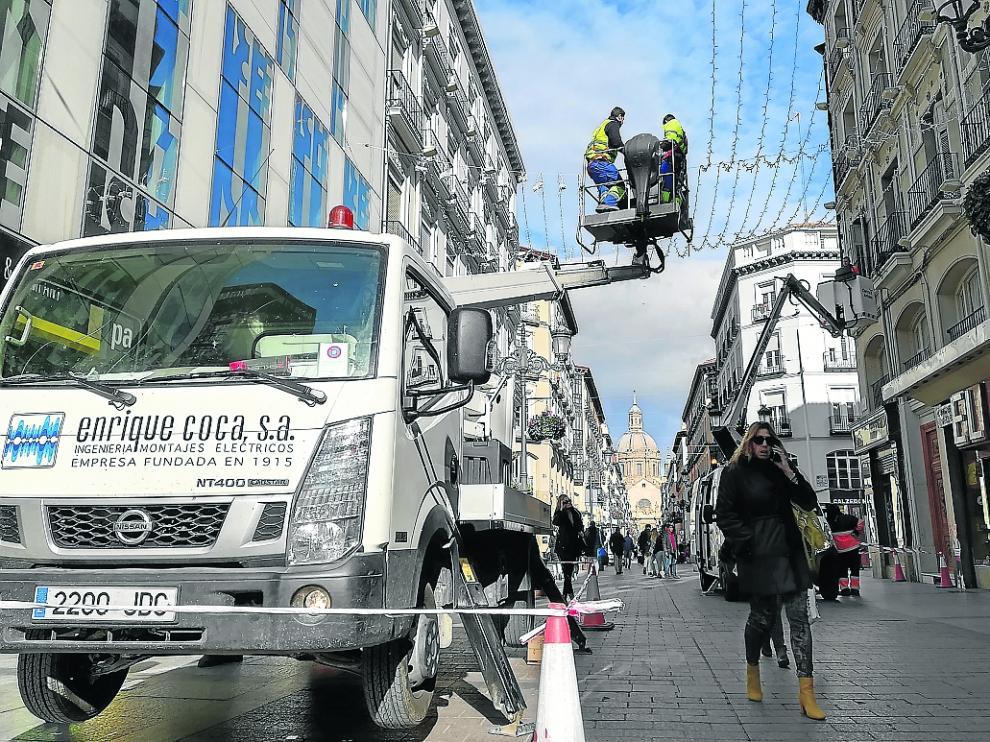 Los operarios ultiman la instalación de las luces de Navidad en la calle de Alfonso I.