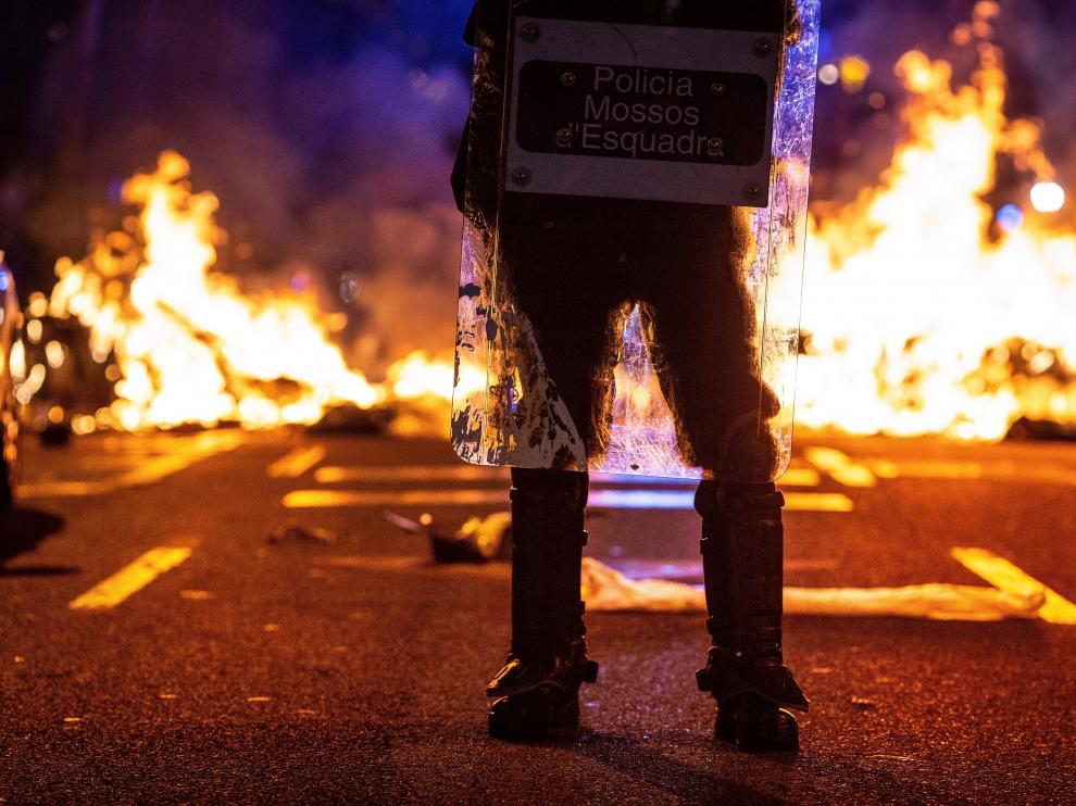 Un mosso ante un acto vandálico de los CDR en una calle de Barcelona
