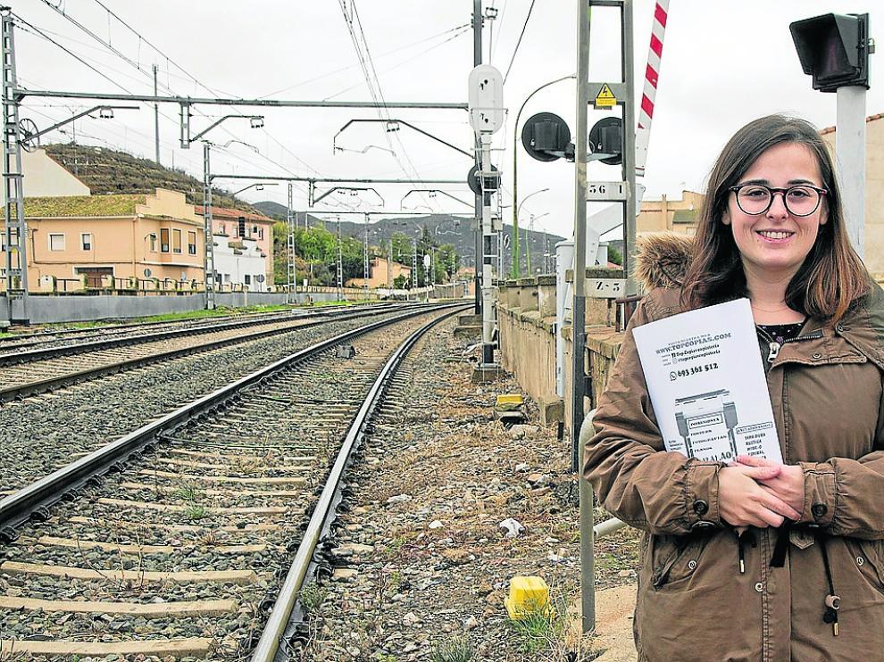 Lierni García, con una carpeta con las firmas que han recogido, en el paso a nivel de Ricla.