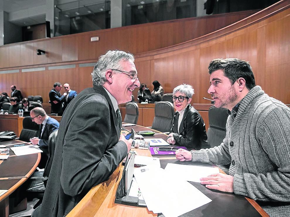 El consejero de Agricultura, Joaquín Olona, y Nacho Escartín (Podemos), este jueves en el pleno.