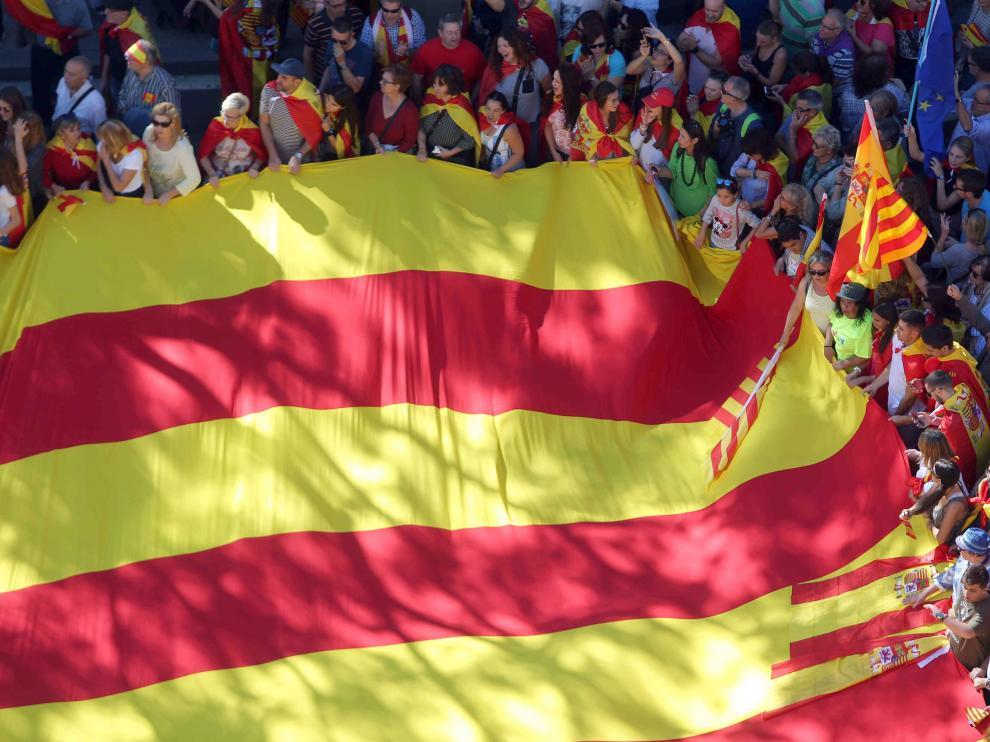 Una gran bandera cuatribarrada desplegada en el centro de Barcelona.