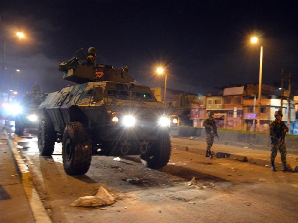 Militares en un tanque y a pie patrullan por las calles de un barrio de Bogotá como se puede ver en esta foto cedida por el Ejército de este país.
