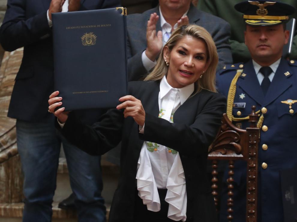 La presidenta interina de Bolivia, Jeanine Áñez, sostiene un documento durante la promulgación de una ley de urgencia este domingo en La Paz