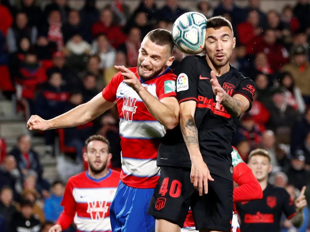 Dario Poveda pugna por un balón aéreo con Domingos Duarte en su debut con el primer equipo del Atlético de Madrid en Granada.