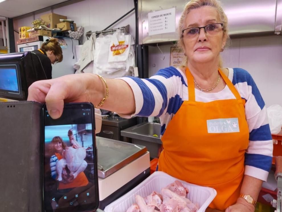 Olga Romeo enseña uno de los enormes pavos que han vendido en su puesto del mercado.