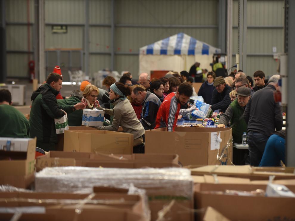 Los voluntarios clasifican todos los productos recibidos en la Feria de Muestras para trasladar después a Banco de Alimentos de Zaragoza..