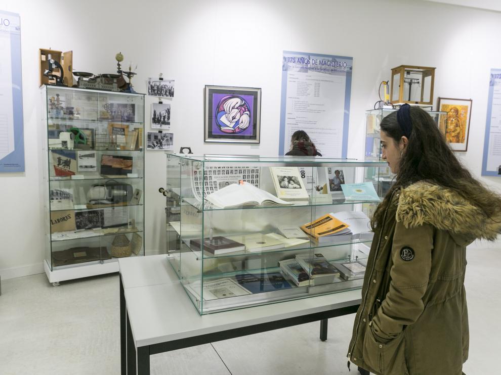 Una joven contempla una vitrina con libros y documentos expuestos