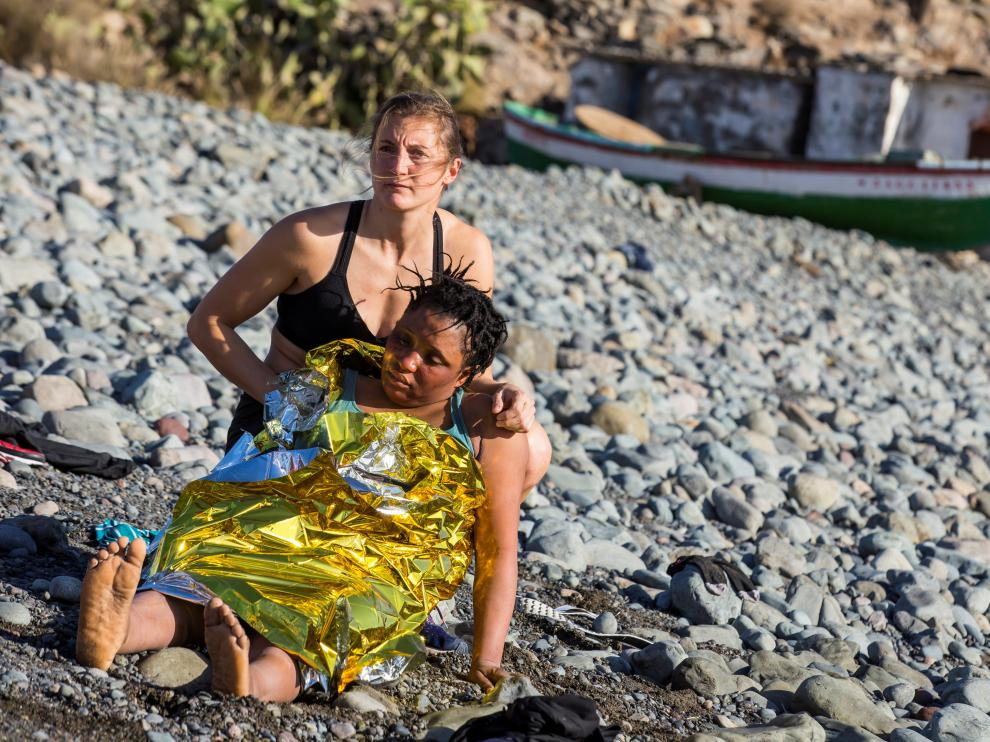 Una bañista atiende a una mujer inmigrante llegada en patera.