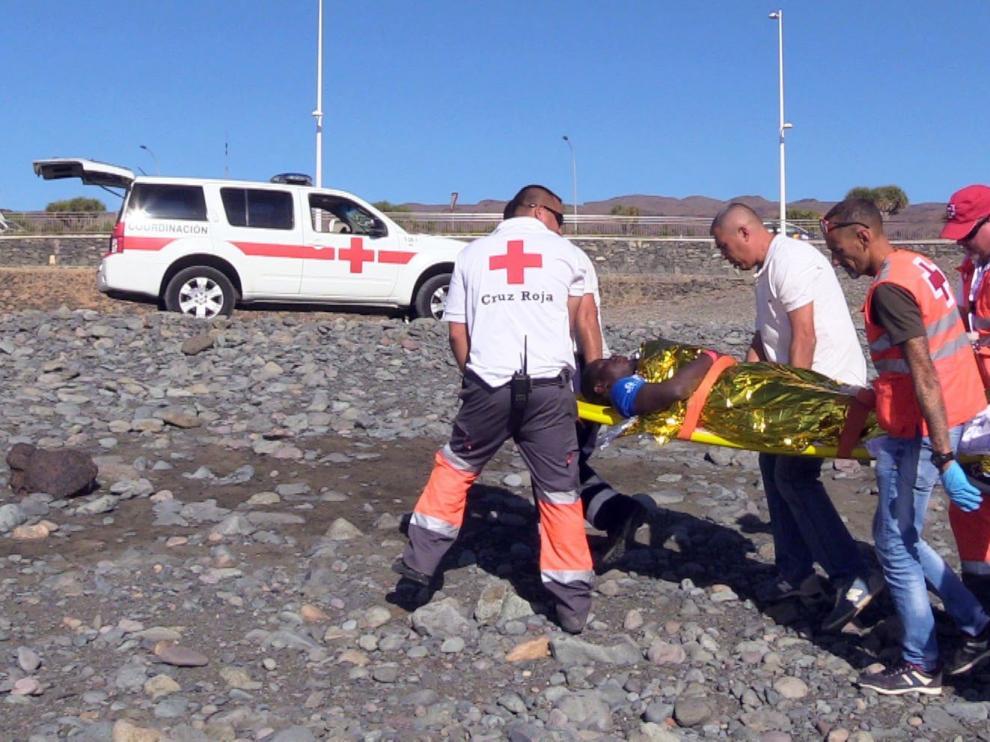 Varios bañistas atienden a un grupo de inmigrantes llegados en patera a Canarias.