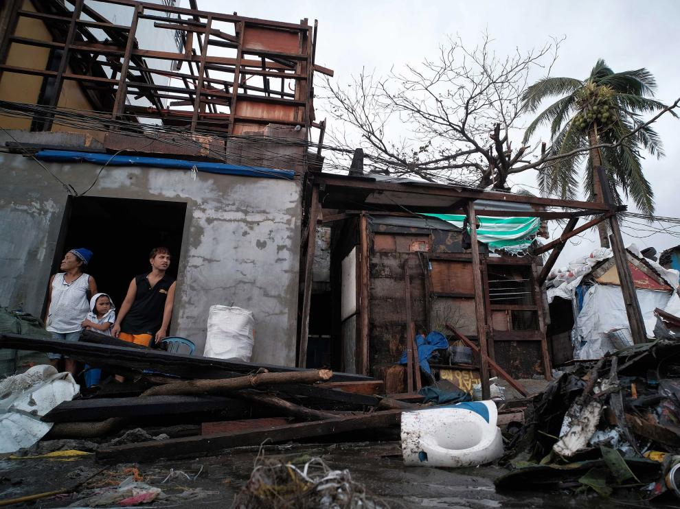 Legazpi City (Philippines), 03/12/2019.- Villagers look on from inside a damaged house in the aftermath of Typhoon Kammuri, in Legazpi city, Philippines, 03 December 2019. Typhoon Kammuri made landfall on 02 December and forced the closure of Ninoy Aquino International Airport in Manila. The typhoon also affected the ongoing Southeast Asian Games. According to the event organizers, several sporting events have been rescheduled or cancelled. (Filipinas) EFE/EPA/ZALRIAN SAYAT Aftermath of Typhoon Kammuri in the Philippines