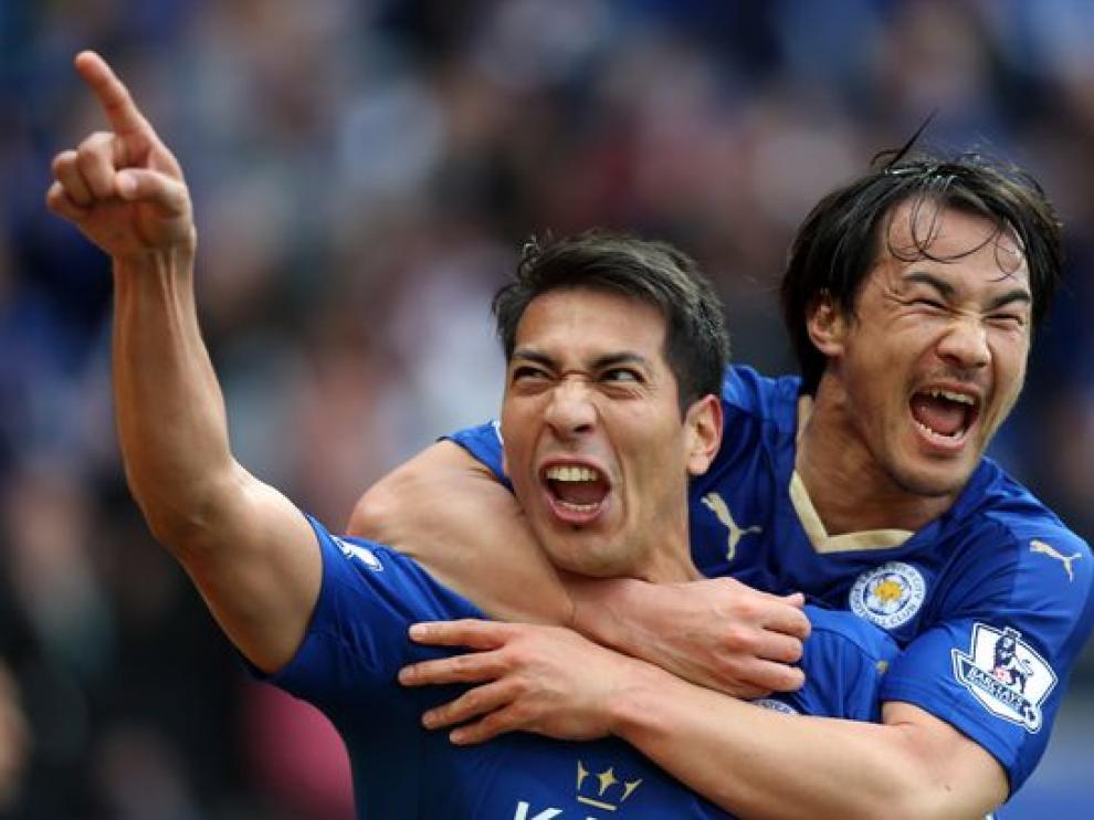 Ulloa y Okazaki se abrazan para celebrar un gol del argentino con el Leicester.