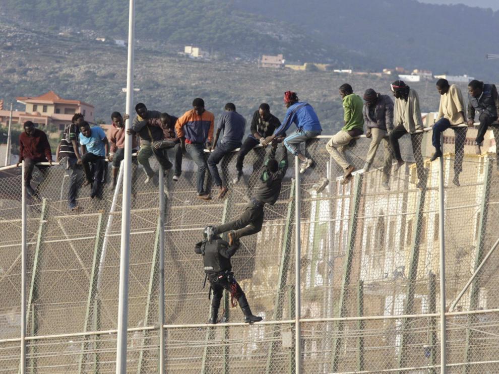Un centenar de inmigrantes permanecen encaramados en la valla fronteriza entre Melilla y Marruecos en una imagen de archivo.