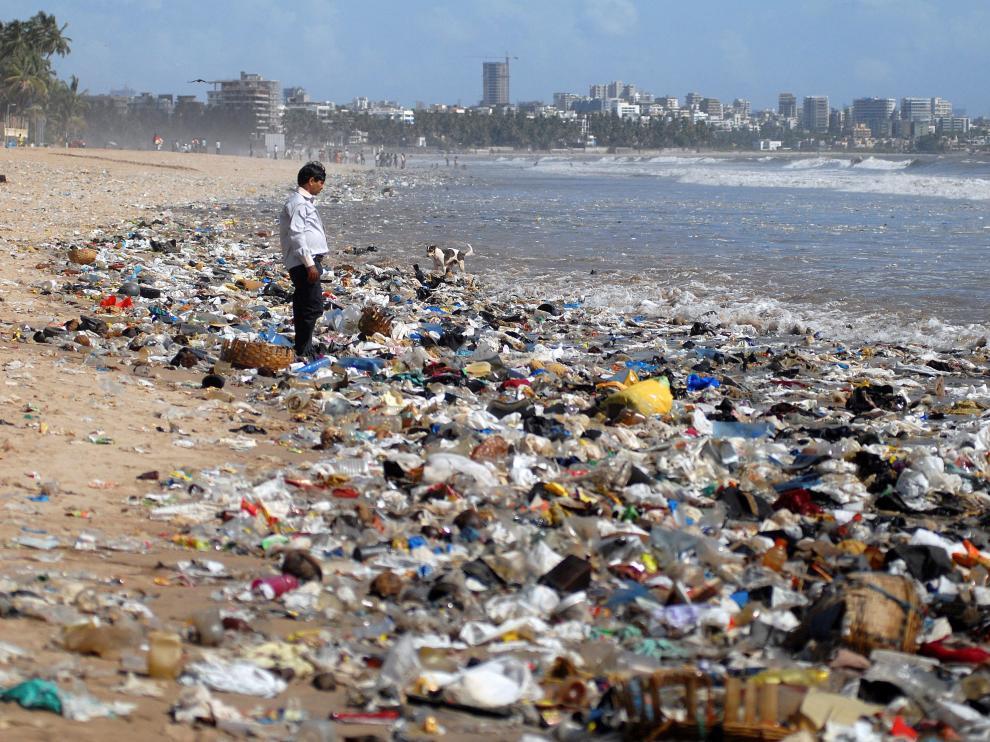 Un hombre observa una montaña de plásticos a orillas del mar Arábigo en Bombay (La India).