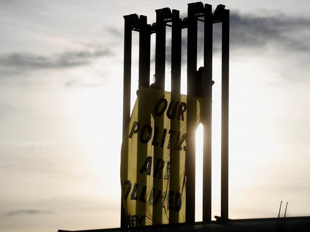 Activistas de Greenpeace despliegan una pancarta en una torre de iluminación del recinto ferial Ifema.