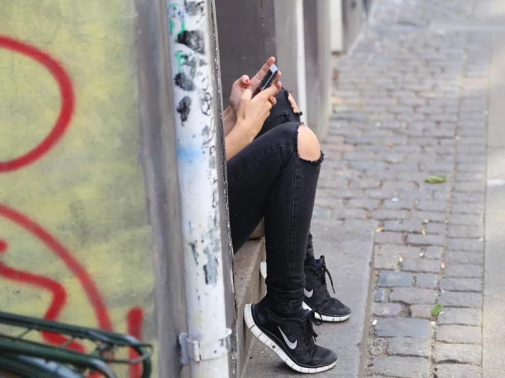 Imagen de archivo de un adolescente con el móvil.