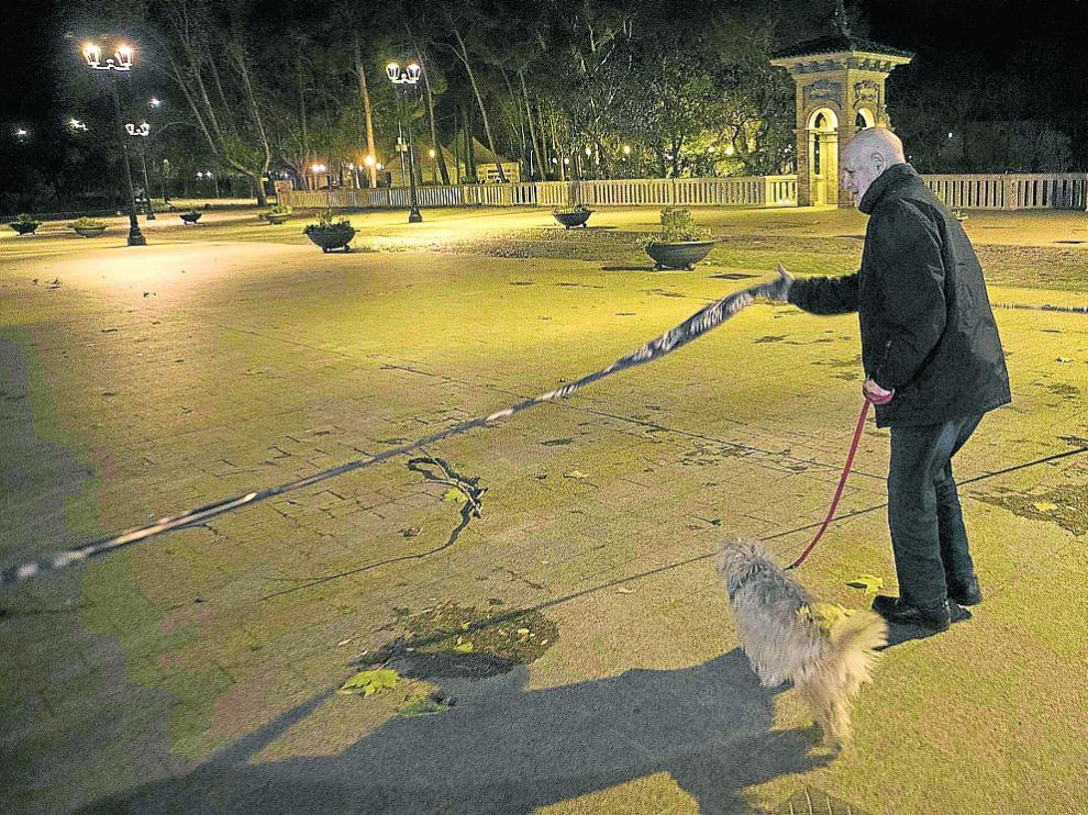 Un vecino levanta la cinta que impedía pasar al Parque Grande tras ser cerrado por la Policía.