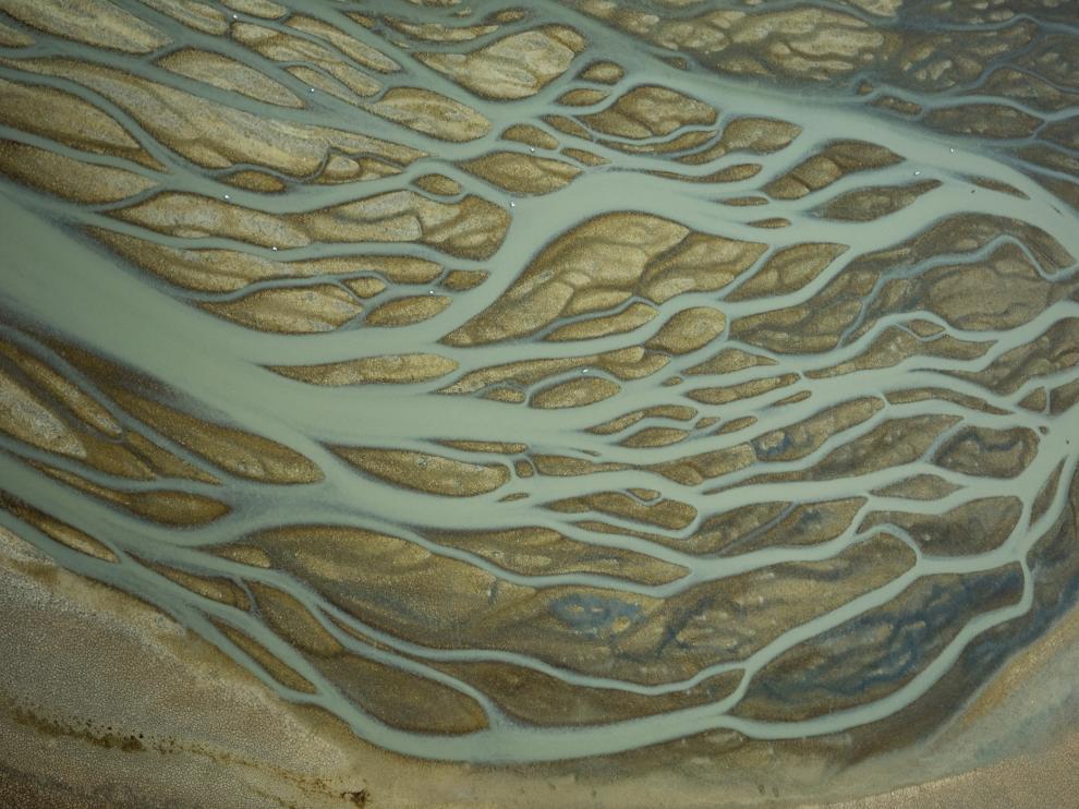 La confluencia de las corrientes hacia un único punto de desagüe distribuye el agua sobre la superficie limosa. Esta imagen de Veta la Palma, en el Espacio Natural de Doñana, muestra las formas de red dendrítica, que recuerdan las sinapsis neuronales.