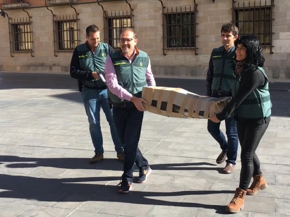 Agentes de la Guardia Civil trasladan la última talla románica recuperada al Museo de Huesca para su estudio.