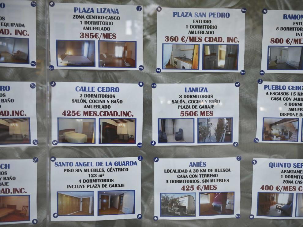Anuncios de pisos de alquiler en el escaparate de una inmobiliaria de Huesca.