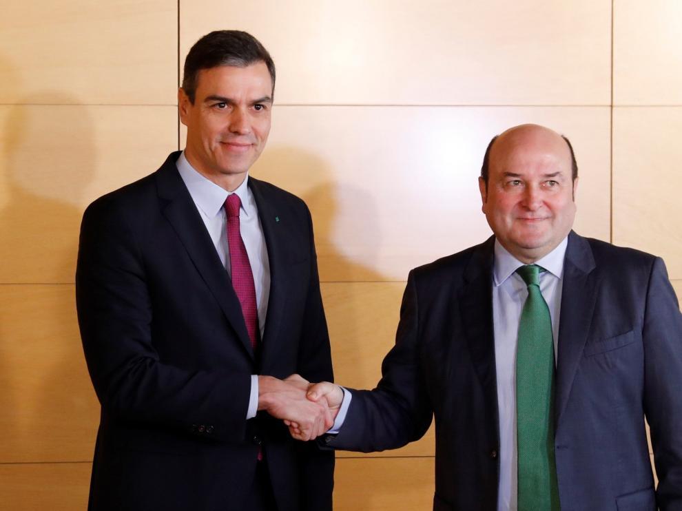 El presidente del Gobierno en funciones, Pedro Sánchez (i), y el presidente del PNV, Andoni Ortuzar (d), durante la firma del acuerdo por el que los nacionalistas vascos votarán a favor de la investidura de Sánchez, este lunes en el Congreso.