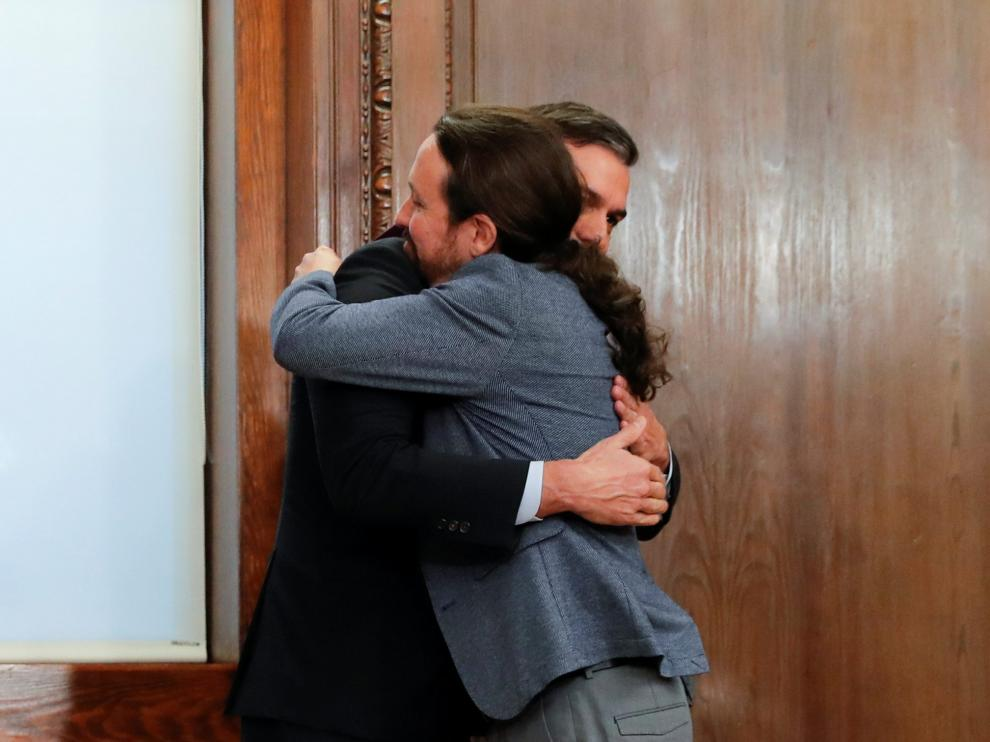 Spain's acting Prime Minister Pedro Sanchez and Unidas Podemos (Together We Can) leader Pablo Iglesias embrace as they present their coalition agreement at Spain's Parliament in Madrid, Spain, December 30, 2019. REUTERS/Susana Vera [[[REUTERS VOCENTO]]] SPAIN-POLITICS/