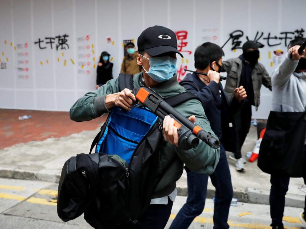 A plain-cloth police officer holds a weapon to disperse anti-government protesters during a demonstration on New Year's Day to call for better governance and democratic reforms in Hong Kong, China, January 1, 2020. REUTERS/Tyrone Siu [[[REUTERS VOCENTO]]] HONGKONG-PROTESTS/