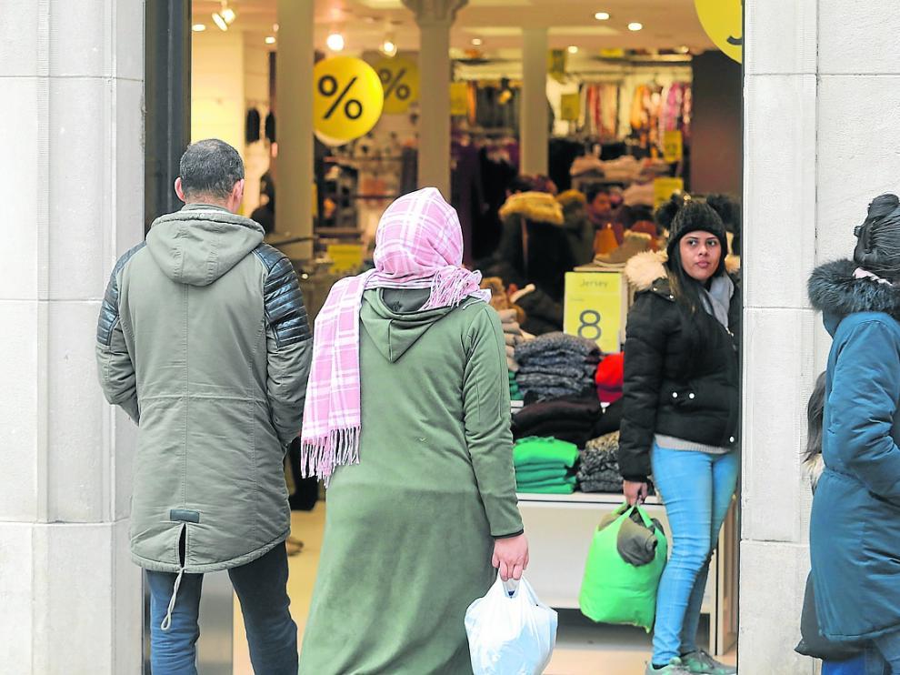 Una pareja de procedencia extranjera entrando ayer en una tienda del Coso Alto de Huesca.