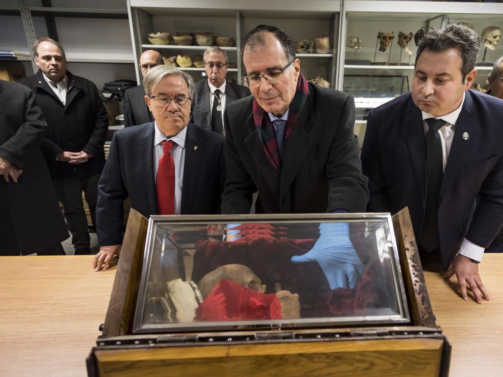 El antropólogo forenses Salvador Baena revisa el interior de la urna con los retos en la Facultad de Medicina, al lado del Justicia de Aragón, Ángel Dolado, y el secretario de la Hermandad Sangre de Cristo, Ricardo Marzo.