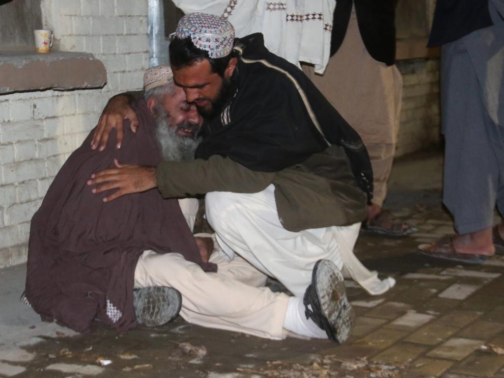 Un hombre consuela a otro en la morgue de Quetta tras la explosión en la mezquita.
