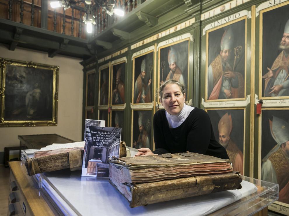Ester Casorrán, con su libro recién publicado y documentos antiguos, en el Archivo Capitular del Pilar