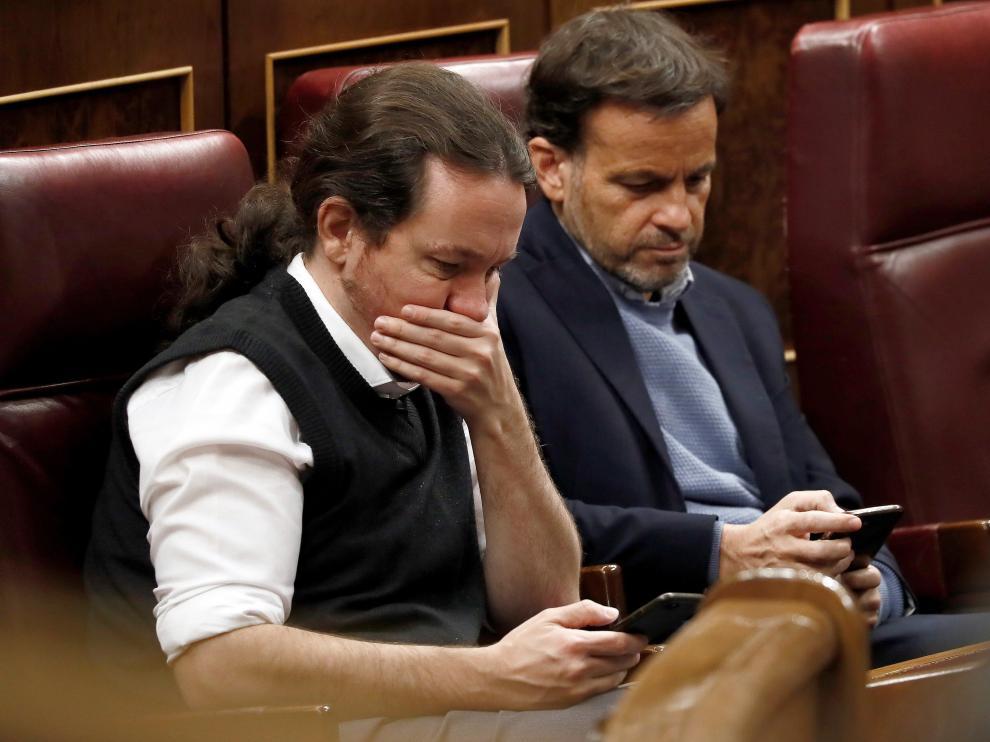Pablo Iglesias y Jaume Asens, de Podemos, consultan el móvil en el Congreso.