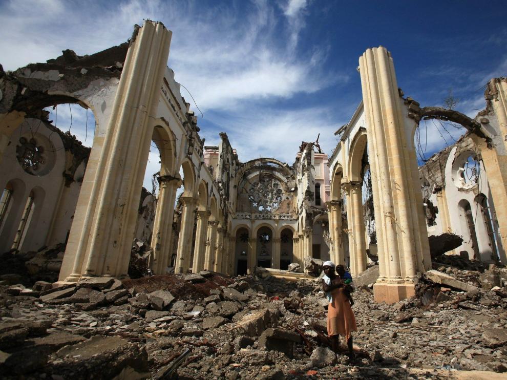 Una mujer camina en medio de los escombros en noviembre de 2010 y ese mismo lugar actualmente