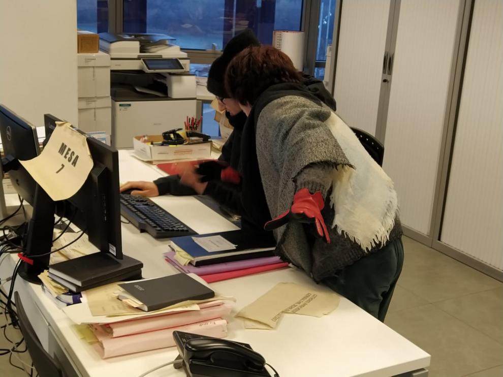 Varios funcionarios trabajando con guantes y gorros en los Juzgados de Zaragoza.