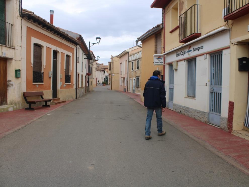 Un vecino de Torrellas pasea por delante de la oficina bancaria del pueblo