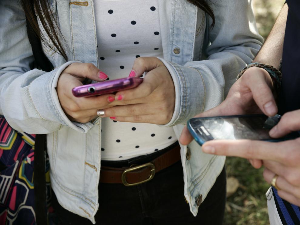 Dos adolescentes usando el móvil.