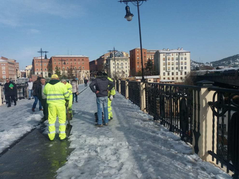 Operarios de Fomento retiran la nieve y el hielo que cubre el Viaducto Viejo de Teruel para evitar caídas.