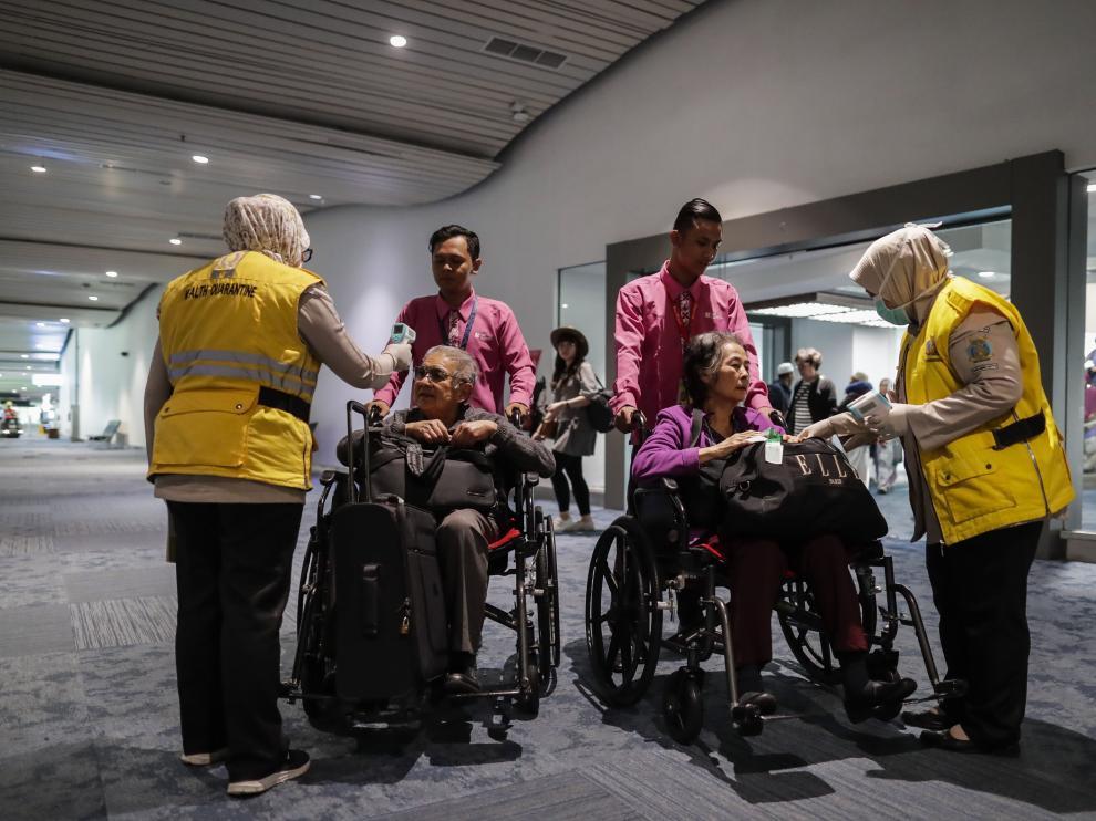 Personal de un aeropuerto internacional de Indonesia mide la temperatura a los pasajeros que llegan que llegan