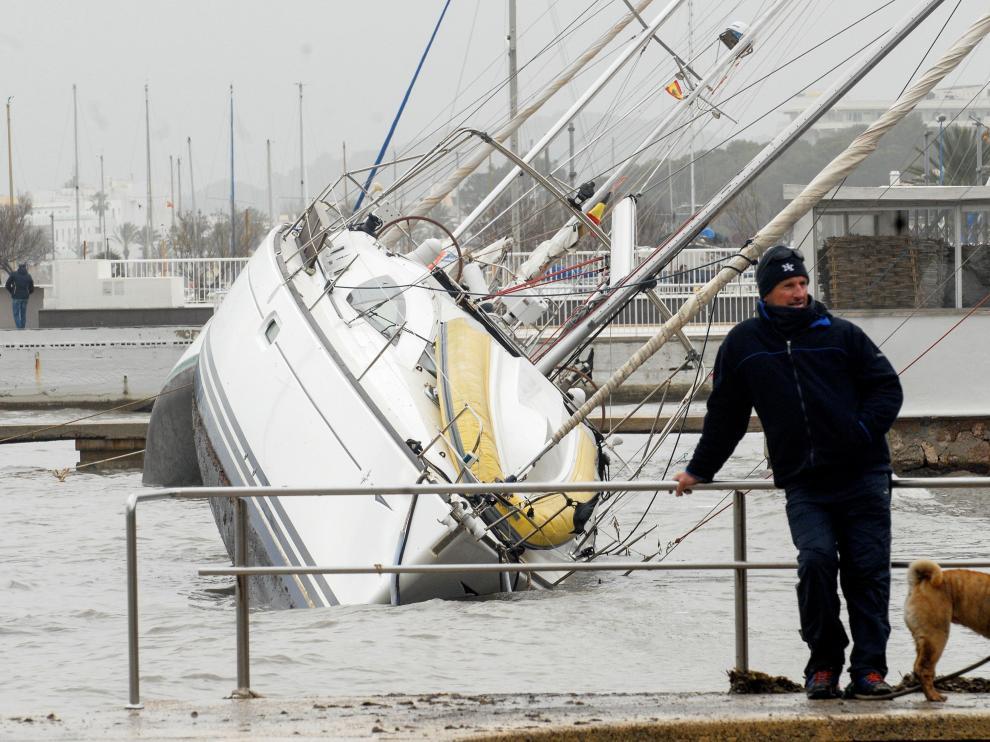 Un hombre observa las embarcaciones arrastradas por la borrasca al Port de Pollença, en Mallorca