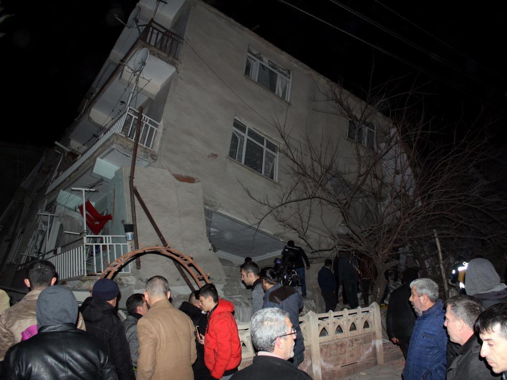 Varias personas, delante de un edificio colapsado en la ciudad de Elazig, afectada por el terremoto.