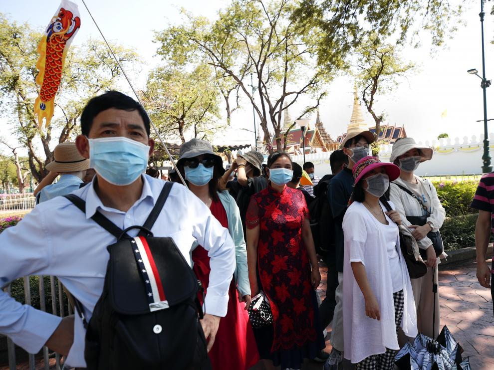 Turistas chinos llevan mascarillas durante la visita al Gran Palacio en Bangkok (Tailandia)