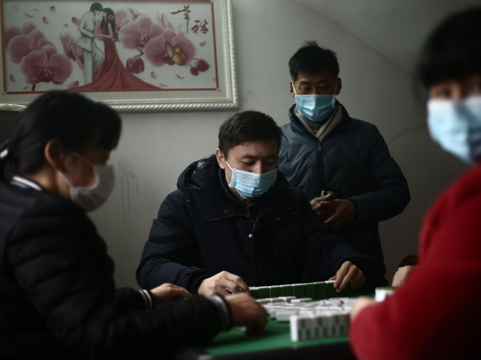 Jianli (China), 25/01/2020.- Masked family members play a board game at home in Jianli county, Hubei province, China, 25 January 2020 (issued 30 January 2020). China announced on 27 January that the Spring Festival holiday would be extended to 02 February 2020 after the coronavirus outbreak spread across the country. The virus, which originated in the Chinese city of Wuhan, has so far killed more than 160 people and infected around 6,000, mostly in China. EFE/EPA/LIU TAO CHINA OUT Spring Festival in Hubei province amid coronavirus lockdown