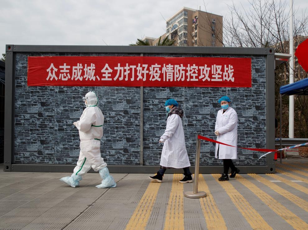 Personal de un hospital con ropa protectora camina hacia un punto de control en la zona de exclusión de la provincia china de Hubei