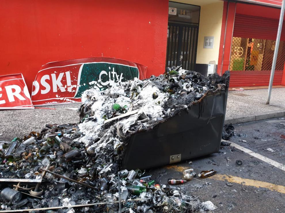 Los restos de los contenedores quemados este domingo por la mañana. El fuego ha afectado a la fachada de un supermercado, dos motos y una vivienda.